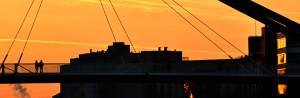 Zwei Menschen auf einer Brücke bei Sonnenuntergang